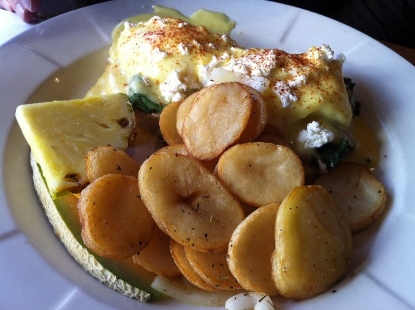 Sicilien Benedict: Two poached eggs on an English muffin with sundried tomatoes, goat cheese and hollandaise sauce served with potatoes and fruits