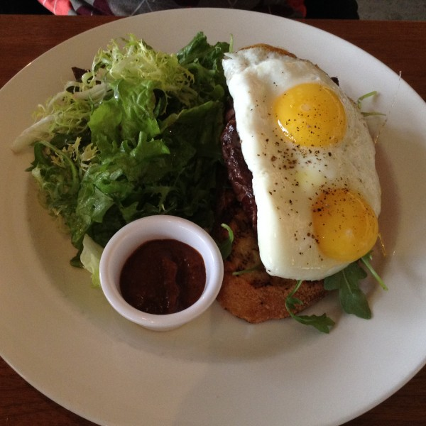 The Manhandler: Sliced striploin steak on toasted garlic sourdough with arugula & two eggs sunny side up