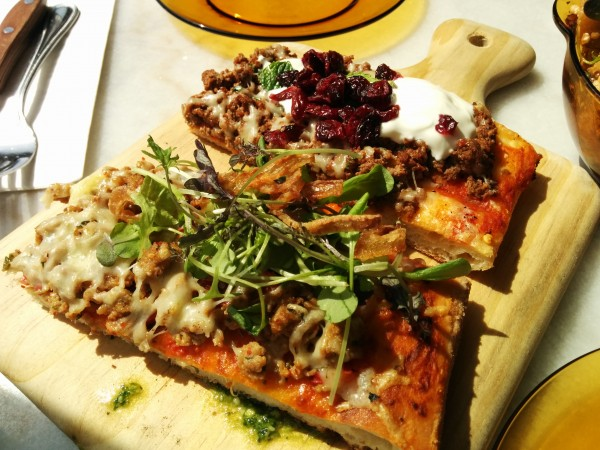Moroccan Pizza with Lamb, Spices, Tzatziki, Cranberries and Chicken Pizza with Peppers, Sundried Tomatoes, Feta, Pesto